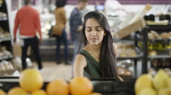 4K Cheerful ethnic woman buying fresh fruit in the supermarket Stock Footage