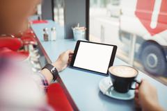 Cropped image of person holding tablet with coffee at restaurant Stock Photos