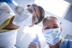 Dentist and dental assistant in surgical mask holding dental tools Stock Photos
