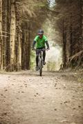 Front view of mountain biker riding on dirt road in forest Stock Photos