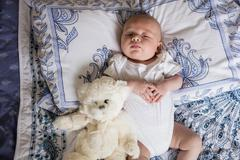 Baby sleeping on bed with teddy bear in bedroom at home Stock Photos