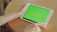 Woman looking at tablet computer with green screen in cafe Stock Footage