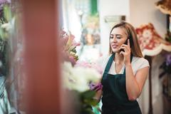 Female florist talking on mobile phone while arranging flowers Stock Photos