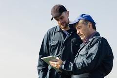 Farm workers discussing over digital tablet against clear sky Stock Photos