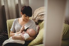 Mother feeding her baby in living room at home Stock Photos