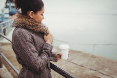 Side view of woman holding disposable coffee cup while standing by railing Stock Photos