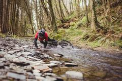 Mountain biker fallen in stream at forest Stock Photos