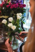 Close-up of  female florist trimming flower leaf at her flower shop Stock Photos