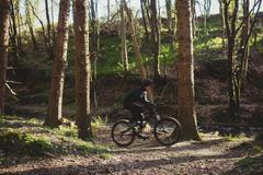 Mountain biker riding bicycle amidst trees in forest Stock Photos