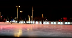 The ice rink changes its color. People of all ages cheerfully pass Stock Footage