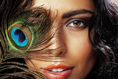 Young sensitive brunette woman with peacock feather eyes close up on green Stock Photos