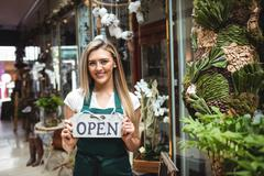 Female florist holding open signboard outside the flower shop Stock Photos