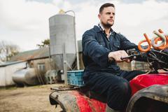 Smart farmer riding quadbike on field against silo Kuvituskuvat