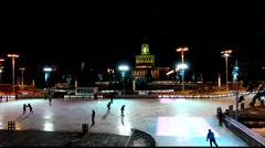 The ice is illuminated by multicolor lights, people skate on the ice rink ENEA Stock Footage