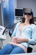 Woman using virtual reality headset during a dental visit in clinic Stock Photos