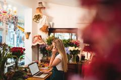 Female florist using laptop while talking on mobile phone in the flower shop Kuvituskuvat
