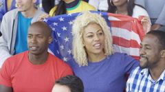 4K Happy friends sitting in the crowd at sports event, woman holding US flag Arkistovideo