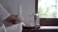 Rustic still life. female hand is pouring milk from a bottle into a glass jar Stock Footage