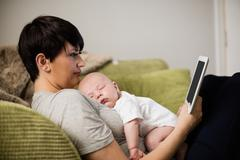 Mother using digital tablet while baby sleeping on her in living room at home Stock Photos