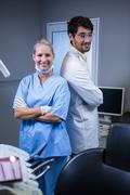 Portrait of smiling dentist and dental assistant standing back to back Stock Photos
