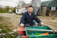 Portrait of young farmer riding quadbike on field against barn Kuvituskuvat