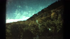 1967: remote mountain lake superimposed over wooded hillside. COLORADO Stock Footage