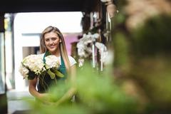 Portrait of female florist holding bunch of flowers at her flower shop Stock Photos