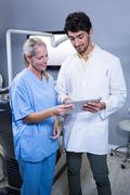 Dentist and dental assistant working together on a tablet at the dental clini Stock Photos