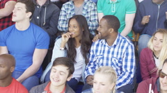 4K Crowd cheering on their team at sports event, focus on young couple Stock Footage