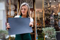 Female florist holding blank signboard outside the flower shop Stock Photos