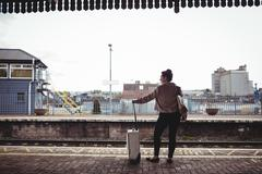 Full length of woman standing at railroad station platform Stock Photos