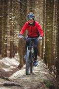 Front view of mountain biker riding on dirt road in woodland Kuvituskuvat