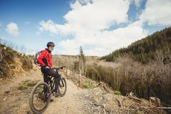 Biker riding bicycle on dirt road at mountain Stock Photos