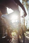 Low section of mountain biker riding on dirt road in forest Stock Photos