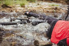 Low section of mountain biker fallen in stream at forest Stock Photos