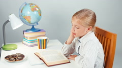 Schoolgirl child reading a book in the evening and eating chocolate cookies Stock Footage