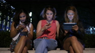 Group of three female friends sat down engaged in their digital devices Stock Footage