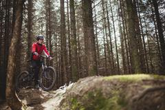 Mountain biker with bicycle amidst trees in woodland Stock Photos