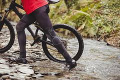 Low section of mountain biker crossing stream in forest Stock Photos