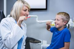 Smiling dentist and patient brushing their teeth at the dental clinic Stock Photos