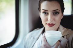 Portrait of young woman holding disposable cup by window in train Stock Photos