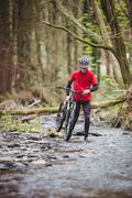 Front view of biker holding bicycle while walking in stream at forest Stock Photos