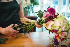 Mid section of female florist trimming flower stem at her flower shop Stock Photos