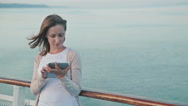 Woman using tablet on deck of cruise ship at sunrise Stock Footage