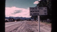 1967: distance sign at the edge of town notes the miles to other towns COLORADO Stock Footage