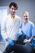 Dentist and dental assistant smiling at camera at the dental clinic Stock Photos