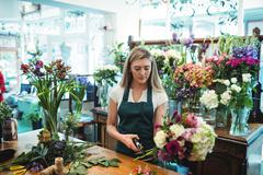 Female florist trimming flower stem at her flower shop Stock Photos