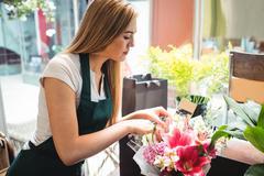 Female florist arranging flower bouquet in the flower shop Stock Photos