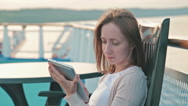 Woman with pc digital tablet sitting on deck of cruise ship at sunrise Stock Footage