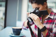 Woman photographing coffee cup while standing at restaurant Stock Photos